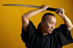 Samurai in black kimano raised his sword up, on a yellow background royalty free stock photo