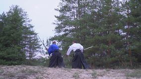 Samurai in a blue kimono with a katana repels a warrior`s attack in a white black kimono with a halberd. The battle of two Japanese warriors in a coniferous stock video footage