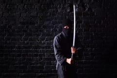 Samurai de Ninja con katana en actitud del ataque en un fondo oscuro de la pared de ladrillo foto de archivo