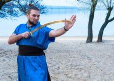 Samurai en kimono, bollo y palillos azules en el entrenamiento principal con la espada y la mirada lejos foto de archivo libre de regalías