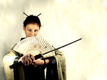 Samurai girl. In kimono with short sword and fan Royalty Free Stock Photos