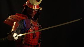 A samurai man in a beautiful red armor, helmet and red defensive mask of a demon pulls out a sword from its scabbards on. A samurai man in a beautiful red armor stock footage