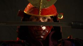 A samurai man in beautiful red armor and a mask examines the katana that pulls out of the scabbard. A samurai man in beautiful red armor and a demon mask stock footage