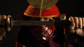 A samurai man in beautiful red armor and a mask pulls out of its scabbards katana sword. A samurai man in beautiful red armor and demon mask pulls out of its stock video footage