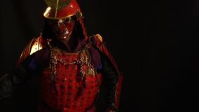 A samurai man in a beautiful red armor and a red defensive mask of a demon pulls the katana out of the sheath and holds. The samurai in red armor and a mask is stock video