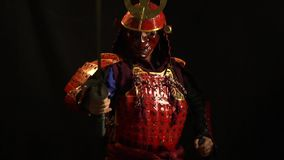 A samurai man in red armor and a defensive mask in the form of a demon stands with a katana in his hands, bit slow. A lonely samurai wearing a mask and red armor stock video footage