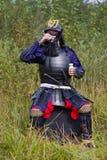 Samurai nella causa bevente dell'armatura dalla tazza Immagini Stock Libere da Diritti