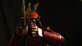 A samurai in red armor, a helmet and a defensive mask in the form of a demon catches the palm of the katana and selects. Samurai in armor selects katana from the stock video