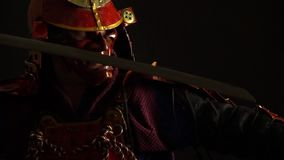 Samurai in a red armor and helmet demon mask becomes a defensive pose with a katana. Samurai in armor stands with a sword in his hands stock footage