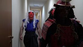 A samurai in red armor and a helmet and a sheathed in a sheath walks down the corridor with two monsters in demon masks. Samurai in red armor and mask comes with stock video footage