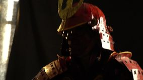 Samurai in red armor and mask attacks katana. Samurai in red armor, helmet and defensive mask in the form of a demon attack katana stock video