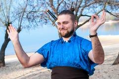 Samurai sorridente bello in kimono blu, stando, ridendo e mostrando meditazione sulla spiaggia fotografia stock libera da diritti