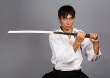 Samurai spirit. Man with katana sword on grey background standing in fighting pose Stock Photo