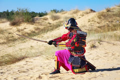 Samurai with sword on the sand. Men in samurai armour on the sand. Original Character Stock Photography
