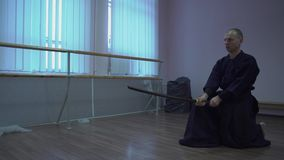 Samurai trains with the sword in the sports hall, refines the kendo technique. Samurai trains with the sword in the sports hall, performs the kata, refines the stock footage