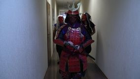 Samurai and two freaks in the demon`s masks are walking along the corridor, slow motion stock video