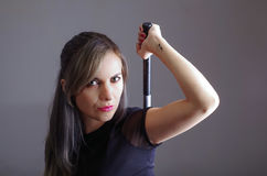 Samurai woman dressed in black clothes holding arm over shoulder grabbing sword hidden behind back, facing camera, ninja Stock Photos