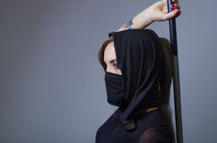 Samurai woman dressed in black with matching veil covering face, holding arm on sword hidden behind back, facing camera Stock Images