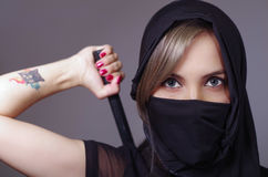 Samurai woman dressed in black with matching veil covering face, holding arm on sword hidden behind back, facing camera Stock Photos