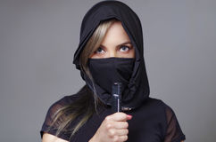 Samurai woman dressed in black with matching veil covering face, holding hand on sword facing camera, ninja concept Royalty Free Stock Photography