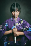 Samurai woman ready to fight. With katana . Studio dark shot Royalty Free Stock Images