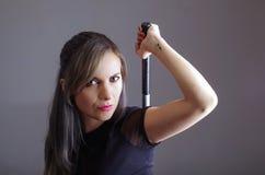 Samuraj kobieta trzyma rękę nad naramiennym chwytać kordzikiem chującym za plecy ubierał w czerni ubraniach, okładzinowa kamera,  Zdjęcia Stock