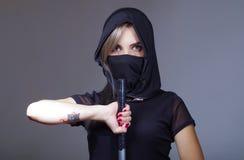 Samuraj kobieta ubierał w czerni z dopasowywanie przesłony nakrycia twarzą, mienie ręka na kordzik okładzinowej kamerze, ninja po zdjęcie royalty free