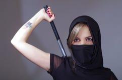 Samuraj kobieta ubierał w czerni z dopasowywanie przesłony nakrycia twarzą, mienie ręka na kordziku chującym za plecy, okładzinow Fotografia Royalty Free