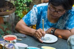 Woman artist painting ceramic pottery in factory house. Samut Sakhon, Thailand - January 21, 2018 : Woman artist painting ceramic pottery in factory house in Royalty Free Stock Photography