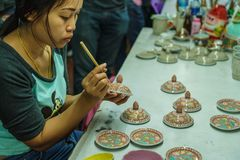 Woman artist painting ceramic pottery in factory house. Samut Sakhon, Thailand - January 21, 2018: Woman artist painting ceramic pottery in factory house where Royalty Free Stock Photography