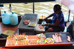 SAMUT SONGKHRAM,泰国- 2014年12月13日:卖在小船的妇女海鲜 免版税图库摄影
