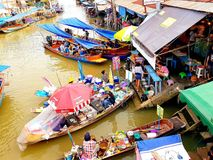 SAMUT SONGKHRAM, THAILAND – JUNE 10, 2018 : Wooden boats busy ferrying people at Amphawa floating market on June 10, 2018. royalty free stock photo