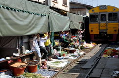 Samut Songkhram, Thailand: Railway Market. Vendors at the Mae Klong Railway Market, their wares and awnings removed from the tracks, wait patiently while the Royalty Free Stock Photos
