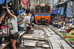 Samut Songkhram, Thailand: Railway Market. As a Thai Railways train approaches all the vendors at the famed Mae Klong Railway Market in Samut Songkhram, Thailand Royalty Free Stock Photos