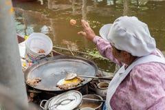 Samut songkram,泰国- 2017年11月11日:烹调食物油煎了蛤蜊-可口泰国食物在Tha Kha浮动市场上, 免版税库存图片