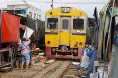 Train passes by the Mae Klong railway tracks market in Samut Songkram, Thailand. Royalty Free Stock Image