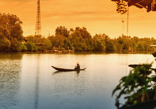 Samuth Songkram, Thailand April 18, 2017: Man rowing a small wooden boat, life along the river. Samuth Songkram, Thailand April 18, 2017: Man rowing a small royalty free stock image