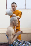 SAMUTPRAKAN TAILÂNDIA 23 DE MARÇO: A monge tailandesa toma um banho a um homem que foto de stock