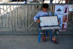 Samutprakarn,泰国- 2017年8月14日:坐和有箱子抽奖券的一个未认出的供营商人待售 免版税库存图片