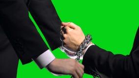 Sanções do negócio, braços acorrentados no fundo de tela verde, conflito econômico video estoque