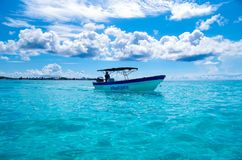 SAN ANDRES, COLOMBIA - OCTOBER 21, 2017: Amazing beautiful view of a man sailing in a boat in an gorgeos blue water, San. Andres Island during a sunny day in Royalty Free Stock Images