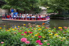 San Antonio River Boat Tour with Flowers. SAN ANTONIO, TEXAS / U.S.A.- AUGUST 17, 2014: Tourist are enjoying the summer by taking a river boat tour on the San Stock Photo
