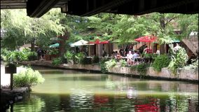 San Antonio River walk 7686. Colorful view of a tree lined section of the landmark San Antonio River Walk in San Antonio, Texas. People enjoying a lazy summer stock footage