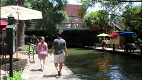 San Antonio River walk 7691. Colorful view of a tree lined section of the landmark San Antonio River Walk in San Antonio, Texas. People enjoying a lazy summer stock video footage