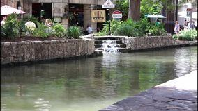 San Antonio River walk 7684. Colorful view of a tree lined section of the landmark San Antonio River Walk in San Antonio, Texas. People enjoying a lazy summer stock video