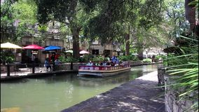 San Antonio River walk 7688. Colorful view of a tree lined section of the landmark San Antonio River Walk in San Antonio, Texas. People enjoying a lazy summer stock footage