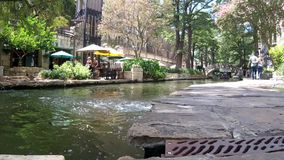 San Antonio River walk 895a. Colorful view of a tree lined section of the landmark San Antonio River Walk in San Antonio, Texas. People enjoying a lazy summer stock video footage