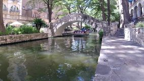 San Antonio River walk - river boat floating by with unidentifiable riders. Colorful view of a tree lined section of the landmark San Antonio River Walk in San stock footage
