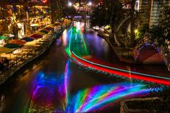 San Antonio Riverwalk at night Christmas time with some skyline. Long exposure streaks colored light through the water from tour barges along the San Antonio stock image