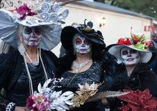SAN ANTONIO, TEXAS - 28 de outubro de 2017 - três mulheres que vestem chapéus e a pintura extravagantes da cara para Dia de Los M imagens de stock